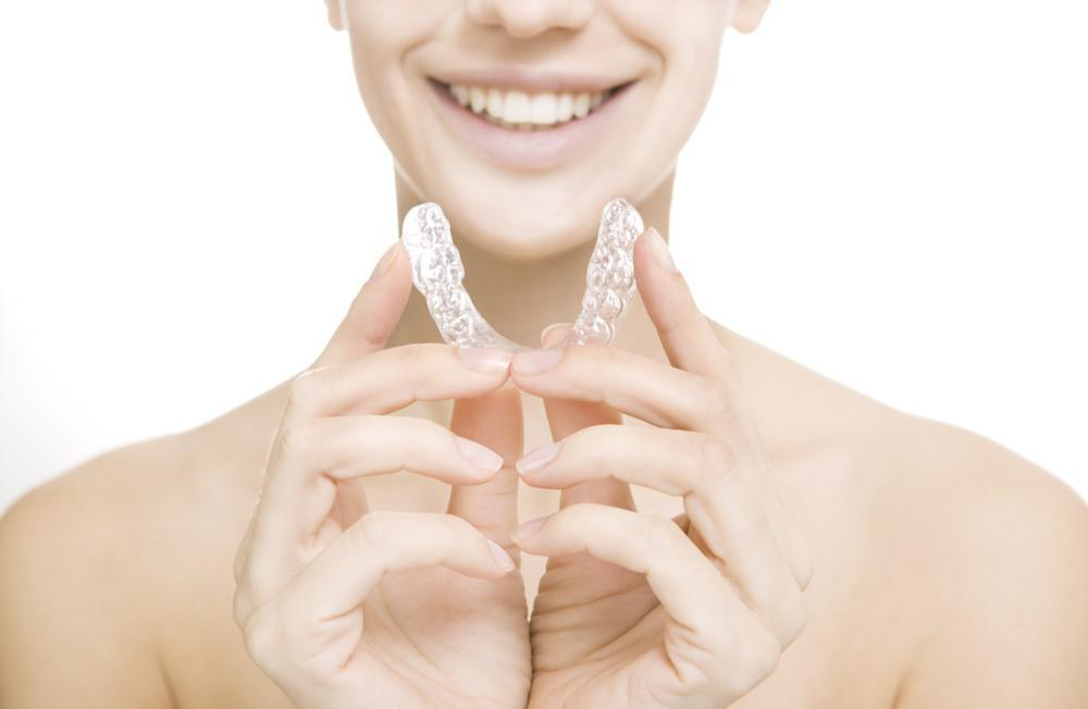 woman holding clear plastic aligner & smiling I invisalign wilmington de