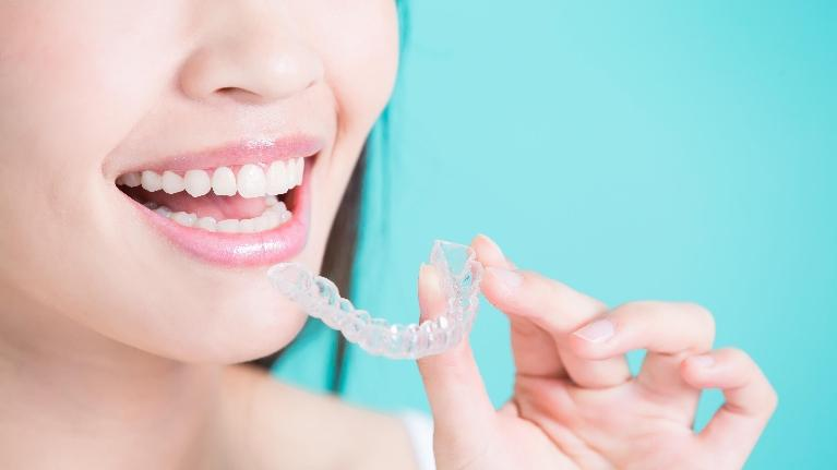a woman holding up an Invisalign aligner | Wilmington DE Invisalign