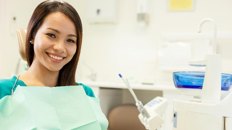 a woman smiles in the dental chair | wilmington de dentist