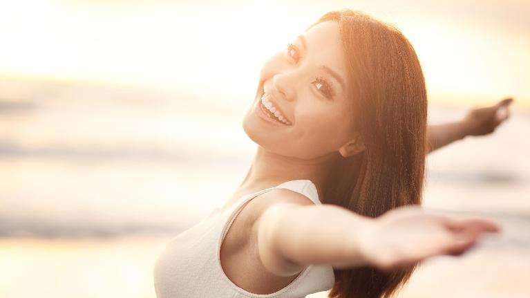 a woman smiles and embraces the sunset | Cosmetic Dentist Wilmington DE