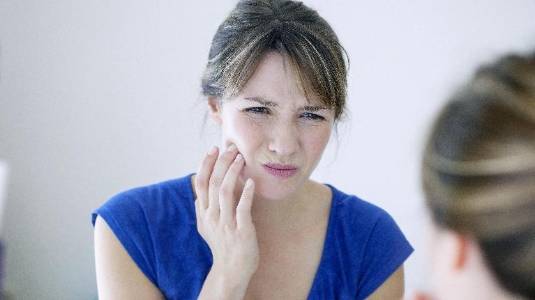 a woman looks in the mirror and holds her hand up to her jaw in pain | Wilmington de dentist