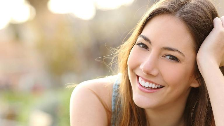 a woman smiles | tooth colored fillings wilmington de