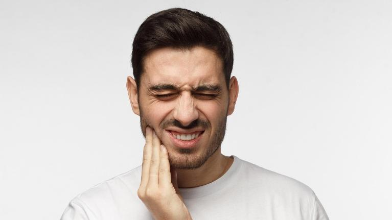 Man with bad tooth pain in need of emergency dentist in Wilmington DE