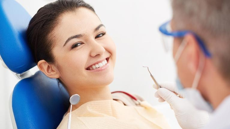 a woman smiles in the dental chair | Wilmington DE Preventive Dentist