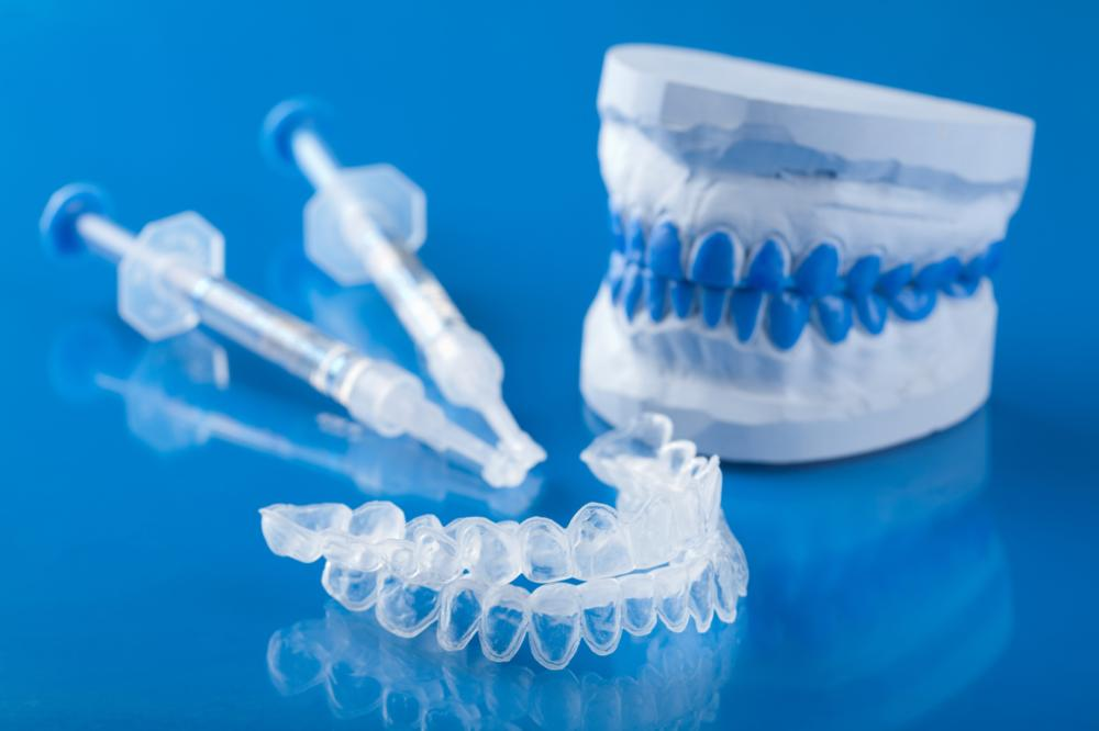 a set of whitening trays and whitening gel on a blue backdrop | Wilmington DE Teeth Whitening