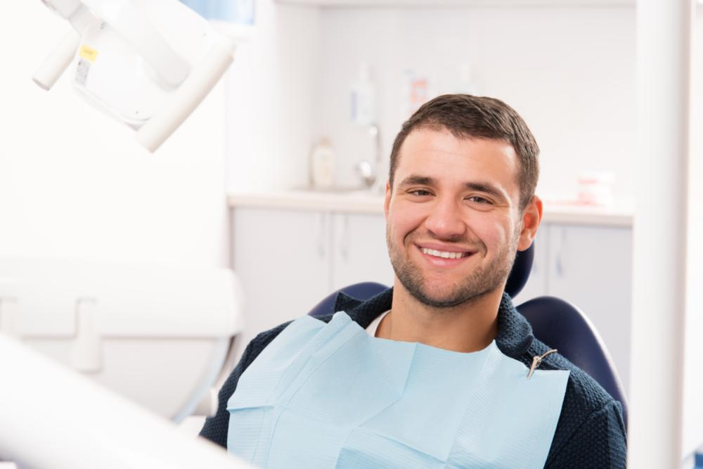 a man smiles in the dental chair | Wilmington DE Cosmetic Dentistry