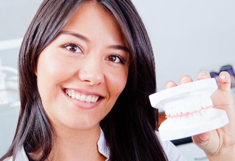 a woman holds up a dental mold | General Dentist Wilmington DE